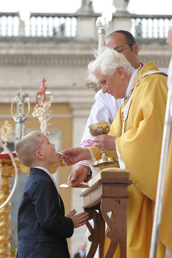 Uma criança recebendo a Santa Comunhão das mãos do Papa Emérito Bento XVI