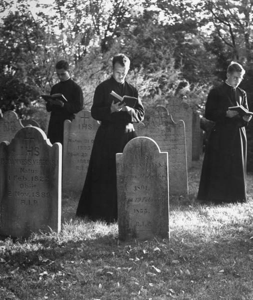 Sacerdotes rezando pelas Almas do Purgatório no cemitério